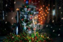 Fles en een glas champagne in Kerstmis achtergrondkerstbomen en slingers Stock Foto's