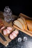 Fles en geschoten glas met wodka met plakken van gerookt vlees op B Stock Afbeeldingen