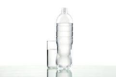 Fles en glas met water op witte achtergrond Royalty-vrije Stock Foto's