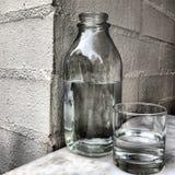 Fles en glas water Stock Afbeeldingen