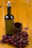 Fles en glas wijn met druiven op hout stock afbeelding