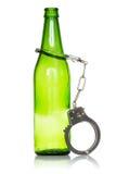 Fles en handcuffs Stock Afbeeldingen
