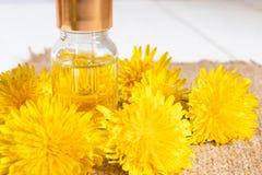 Fles etherische olie met paardebloembloemen in de voorgrond De essenti?le olie van de bloem royalty-vrije stock fotografie