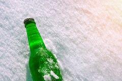 Fles koud bier op de sneeuw royalty-vrije stock afbeeldingen