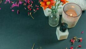 Fles lichaamslotion met bloemen, bloemblaadjebloemen en handdoeken Stock Foto's