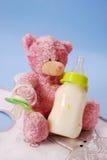 Fles melk voor baby en teddybeer Stock Foto's
