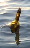 Fles met een geheim bericht in het midden van de oceaan royalty-vrije stock afbeelding
