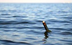 Fles met een geheim bericht in het midden van de oceaan stock afbeeldingen