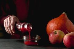 Fles met in hand Amerikaanse veenbes, pompoen en appelen op de lijst Stock Foto's