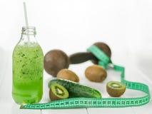 Fles met komkommer smoothies, verspreide kiwi en het meten van band op houten lijst Royalty-vrije Stock Afbeeldingen
