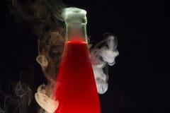 Fles met rode die vloeistof met rook wordt omringd Stock Afbeeldingen