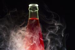Fles met rode die vloeistof met rook wordt omringd Stock Afbeelding
