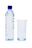 Fles mineraalwater en leeg glas Royalty-vrije Stock Foto