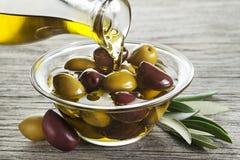 Fles olijfolie het gieten in glas Royalty-vrije Stock Afbeeldingen