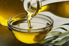 Fles olijfolie het gieten in glas Stock Afbeeldingen