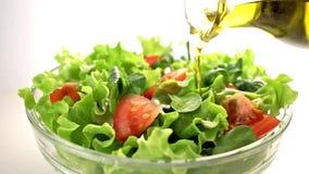 Fles olijfolie het gieten over gemengde salade stock footage