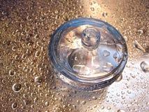 Fles parfum op blauwe en zilveren achtergrond met daling van wat Stock Afbeelding