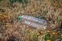 Fles plastiek in het hout wordt geworpen dat stock foto