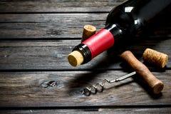 Fles rode wijn met een kurketrekker stock foto