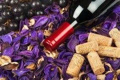 Fles rode wijn op bloembloemblaadjes Stock Fotografie
