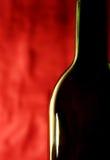 Fles tegen een rode achtergrond Royalty-vrije Stock Afbeelding