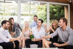Fles van de mensen de knallende champagne met vrienden stock foto