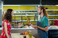 Fles van de winkel de hulp aanbiedende olijfolie aan de klant Royalty-vrije Stock Afbeeldingen