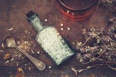 Fles van homeopathische druppeltjes, bos van droge gezonde kruiden en glas van tint of gezonde thee royalty-vrije stock fotografie