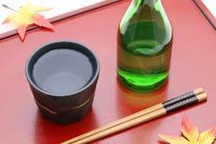 Fles van Japanse shochu en kom op houten dienblad stock afbeeldingen