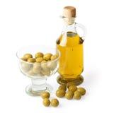 Fles van olijfolie en olijven die op wit wordt geïsoleerdr Stock Foto's