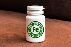 Fles van pillen met ijzer Royalty-vrije Stock Afbeeldingen