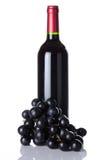 Fles van rode wijn en zwarte druiven Stock Fotografie