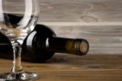 Fles van rode wijn met een glas en kurketrekker op een oude houten lijst royalty-vrije stock foto's