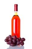 Fles van roséwijn en rode druiven Stock Afbeelding