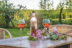 Fles van roze wijn en twee wijnglazen op oude houten lijst outd Royalty-vrije Stock Foto's