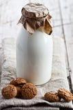 Fles van verse melk en amandelkoekjes Royalty-vrije Stock Foto's