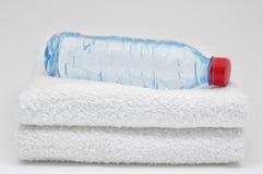 Fles van water en handdoeken op grijze achtergrond Stock Fotografie