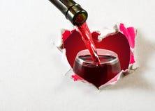 fles van wijn en wijnglas op abstract hartclose-up als achtergrond Stock Foto's