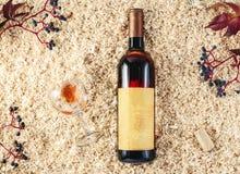 Fles van wijnpresentatie op zaagselachtergrond stock foto