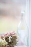 Fles in venster naast roze bloemen Stock Afbeeldingen