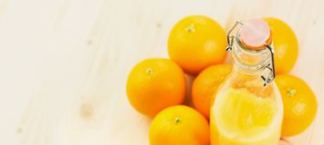 Fles vers gedrukt jus d'orange met sinaasappelen stock afbeelding
