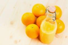 Fles vers gedrukt jus d'orange met sinaasappelen stock fotografie