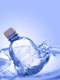 Fles in water stock afbeelding