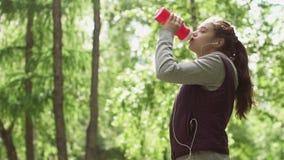 Fles water in de handen van een sportmeisje Jong aantrekkelijk sportvrouw drinkwater in opleiding Langzame Motie stock video