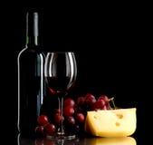 Fles wijn, een bos van rode druiven en een stuk van kaas Royalty-vrije Stock Afbeeldingen