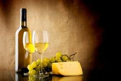 Fles wijn, een bos van witte druiven en een stuk van kaas Stock Foto's
