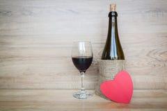 Fles wijn en wijnglas met hart op houten achtergrond Stock Foto