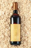 Fles wijn op de zaagselachtergrond stock afbeeldingen