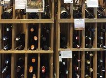 Fles wijnen bij planken het verkopen Stock Afbeelding