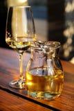 Fles wit wijn en glas op houten lijstbovenkant Glas gekoelde witte wijn op lijst dichtbij het strand Royalty-vrije Stock Afbeeldingen